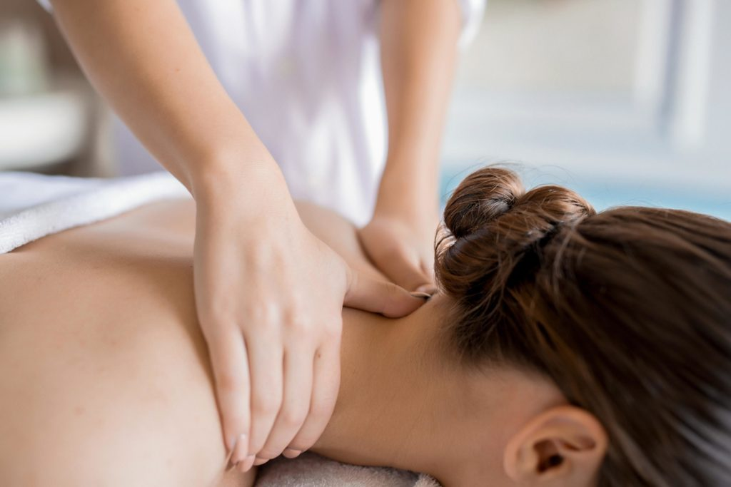 Hands of masseuse massaging neck and shoulders of relaxed client in spa salon